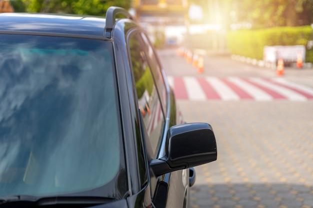 Przód samochodu w kolorze czarnym z przednią szybą i tylnym lusterkiem bocznym parkuj na drodze