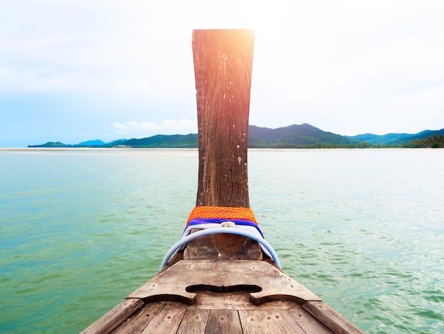 Przód tradycyjnej drewnianej łodzi typu longtail na morzu w kierunku wyspy.