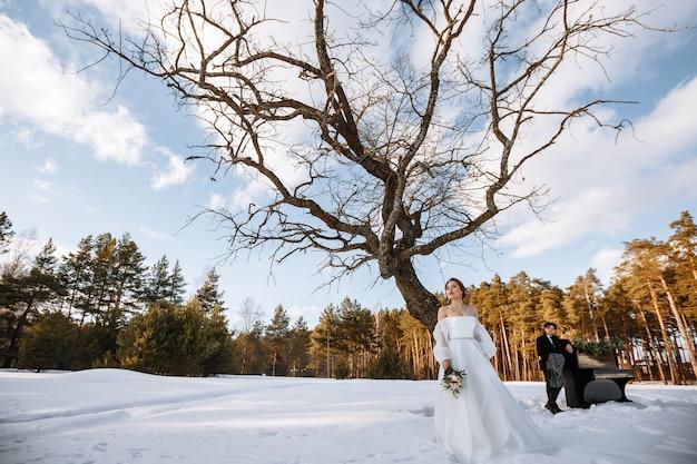 Przy fortepianie stoją dziewczyna w sukni ślubnej i młody mężczyzna. fotografia zimowa