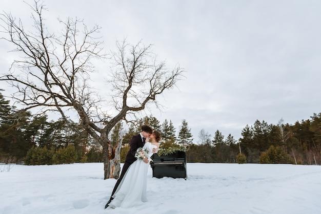 Przy fortepianie stoją dziewczyna w sukni ślubnej i młody mężczyzna.