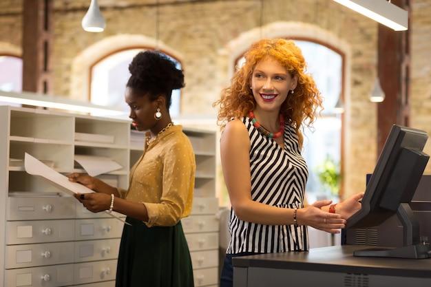 Przy kasie. rudowłosa bizneswoman szlifuje przy biurku kasjera w sklepie papierniczym