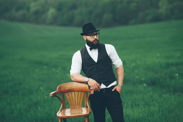 Przy krześle na polu stoi mężczyzna z brodą
