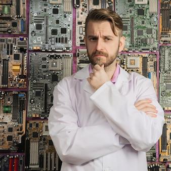 Przy ścianie płyt głównych stoi kontemplacyjny inżynier elektronik