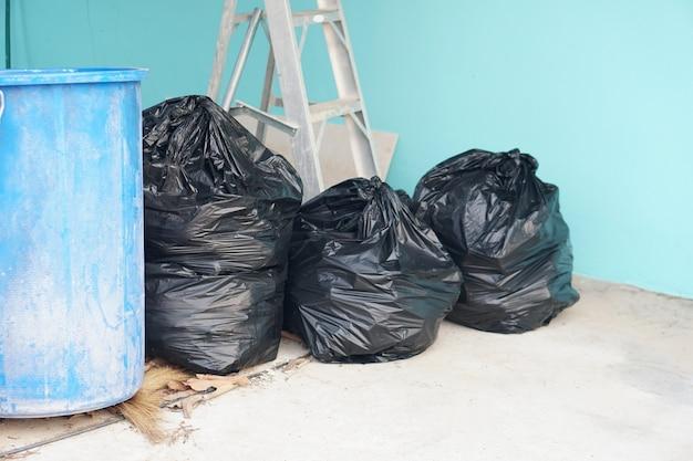 Przy ścianie umieszczono czarny worek na śmieci