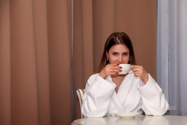 Przy stole siedzi dziewczyna o słowiańskim wyglądzie w płaszczu z białą filiżanką