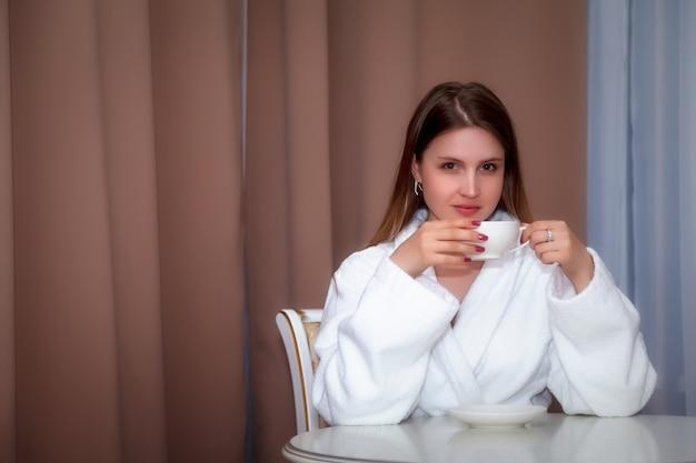 Przy stole siedzi dziewczyna o słowiańskim wyglądzie w płaszczu z białym kubkiem