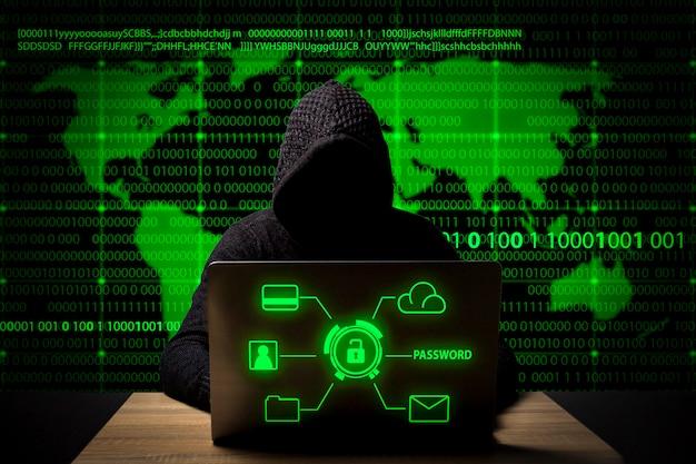 Przy stole siedzi haker w kurtce z kapturem i laptopem