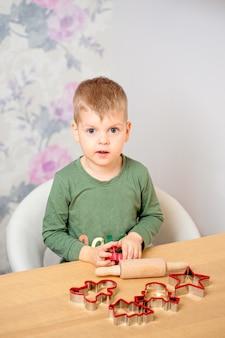 Przy stole siedzi młody chłopak z piernikowymi kształtami i bułką ciasta.