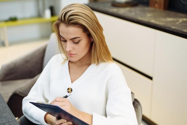 Przy stole siedzi śliczna młoda kobieta i pisze w zeszycie. tworzenie listy zakupów do domu