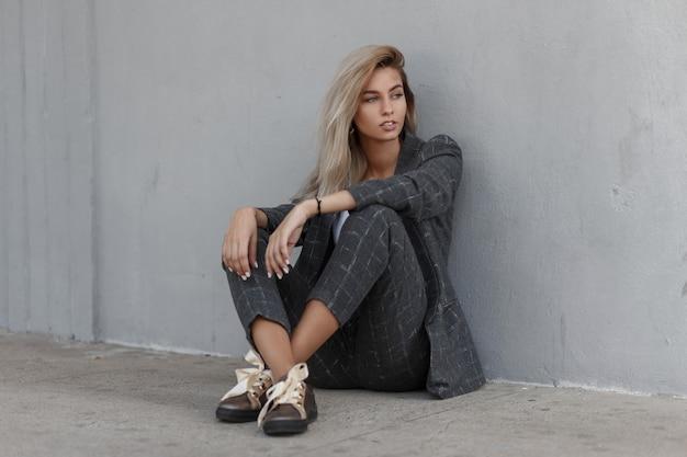 Przy szarej ścianie siedzi dość stylowa młoda blond dziewczyna w surowym garniturze z modną szarą kurtką i spodniami z butami
