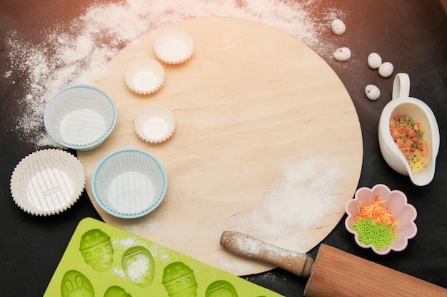 Przybory kuchenne do pieczenia na czarnej ścianie, posypanej mąką. przyciemniane oświetlenie