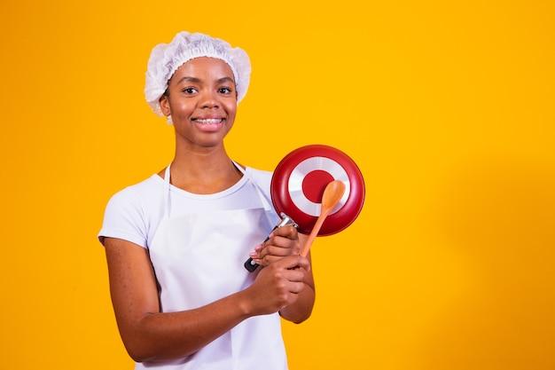 Przybory kuchenne. gotowanie kobieta w kuchni z patelni i drewnianą łyżką. gospodyni waląca pan