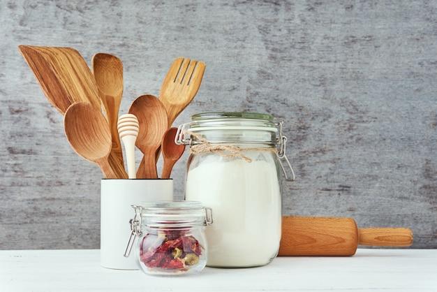 Przybory kuchenne z drewnianymi sztućcami i wałkiem na białym stole