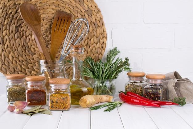 Przybory kuchenne, zioła, kolorowe suche przyprawy w szklanych słoikach na białej ścianie