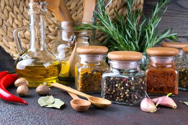 Przybory kuchenne, zioła, kolorowe suche przyprawy w szklanych słoikach na ciemnej powierzchni