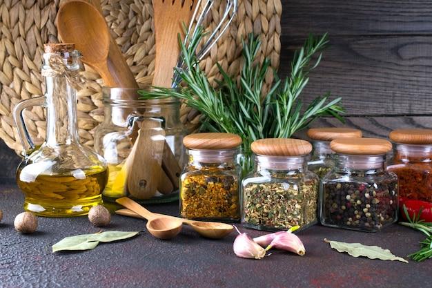 Przybory kuchenne, zioła, kolorowe suche przyprawy w szklanych słoikach