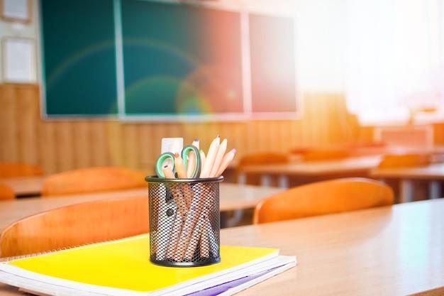 Przybory szkolne do nauki leżą na stole w szkole