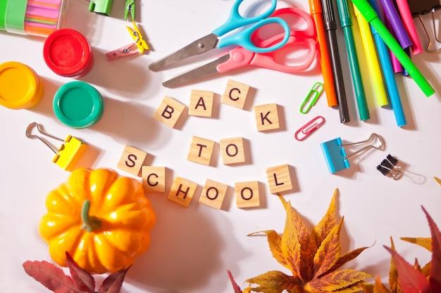 Przybory szkolne, dynia, jesienne liście i tekst do szkoły na białym stole