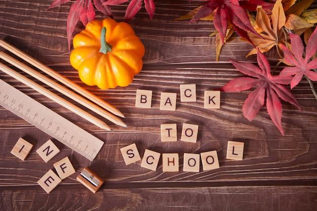 Przybory szkolne, dynia, jesienne liście i tekst do szkoły na drewnianym stole