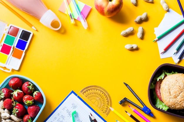 Przybory szkolne dziecka i obiad w plastikowych skrzynkach na żółtym tle
