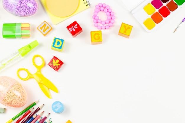 Przybory szkolne, dziecko kreatywność koncepcja płaskie świeckich. różne narzędzia artystyczne dla dzieci na białym pulpicie. skopiuj miejsce
