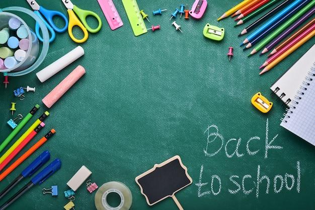 Przybory szkolne i czarna lampa stołowa na zielonej tablicy. koncepcja z powrotem do szkoły. makieta do projektu. skopiuj miejsce. koncepcja edukacji.