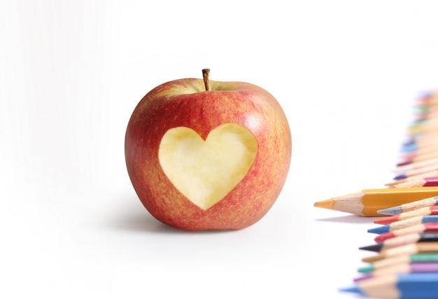 Przybory szkolne i jabłko.