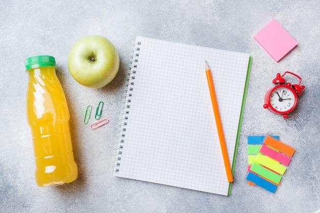 Przybory szkolne i krakersy śniadaniowe, sok pomarańczowy i świeże jabłko