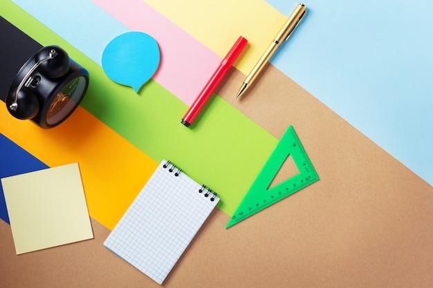 Przybory szkolne i materiały biurowe na abstrakcyjnej powierzchni tła papieru