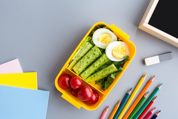 Przybory szkolne i pudełko na lunch z kanapkami i warzywami