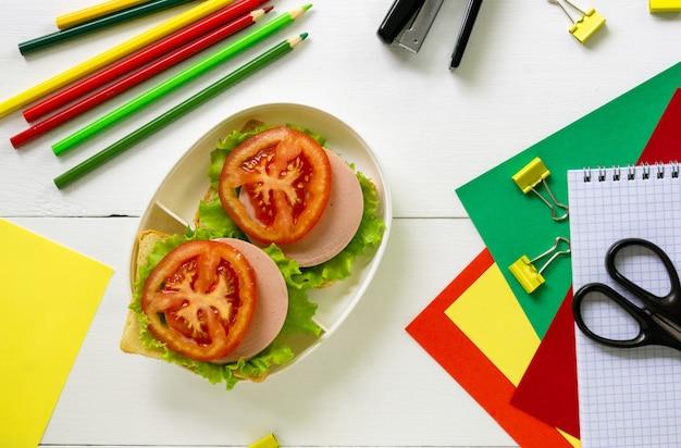 Przybory szkolne i pudełko na lunch z kanapkami na białym tle drewniane