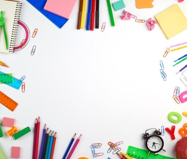 Przybory szkolne: kolorowe drewniane ołówki, naklejki papierowe, spinacze do papieru