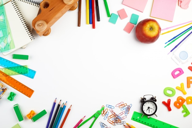 Przybory szkolne: kolorowe drewniane ołówki, naklejki papierowe, spinacze, temperówka