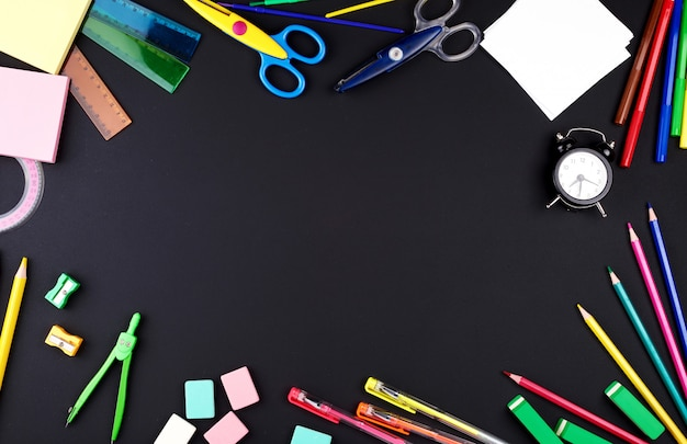 Przybory szkolne: kolorowe drewniane ołówki, notatnik, naklejki papierowe, spinacze, temperówka