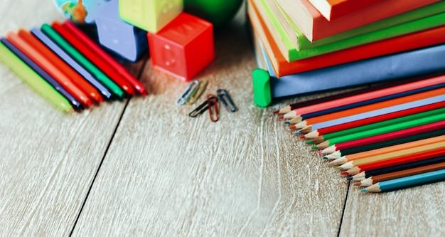 Przybory szkolne leżące na drewnianej podłodze. wraz z książkami, kostkami do gry, ołówkami i markerami tworzą szkolną piosenkę