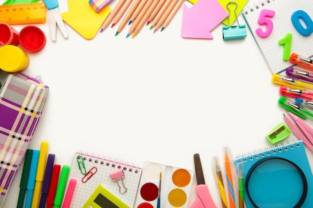 Przybory szkolne na białym tle. powrót do koncepcji szkoły. widok z góry.