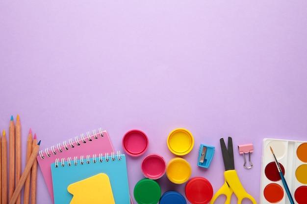 Przybory szkolne na fioletowym tle. powrót do koncepcji szkoły. widok z góry.