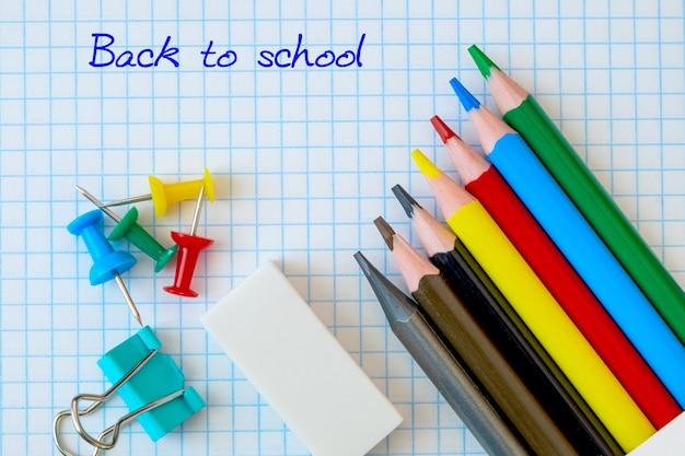 Przybory szkolne na stole z tłem notatnika i napisem powrót do szkoły, kredkami i gumką.