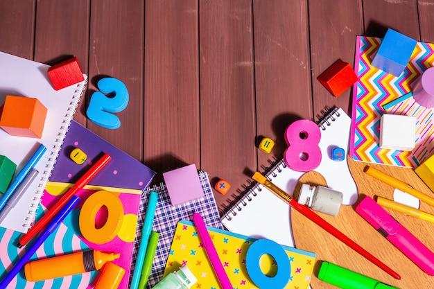 Przybory szkolne na tle drewnianych desek. album, zeszyty, flamastry, pędzle, paleta, drewniane kostki i cyferki. moda twarde światło, ciemny cień, widok z góry