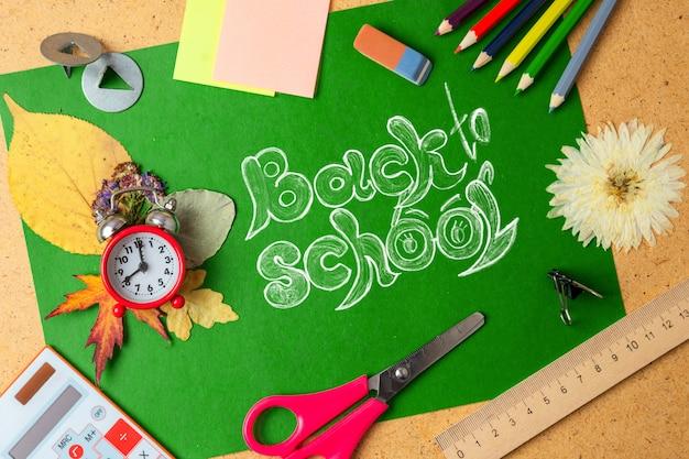 Przybory szkolne na zielonej tablicy.