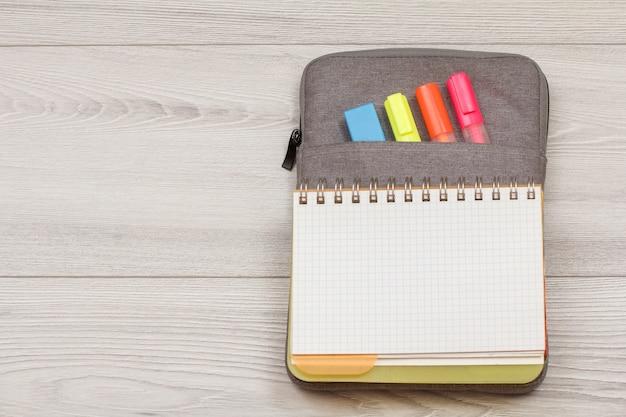 Przybory szkolne. otwórz zeszyt na torbie-piórniku z kolorowymi pisakami i markerem na szarych drewnianych deskach. widok z góry z miejsca na kopię. powrót do koncepcji szkoły