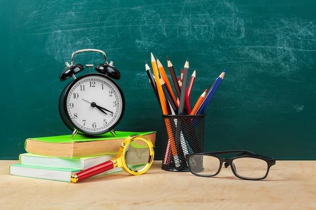 Przybory szkolne. przybory do pisania i budzik. czas na naukę koncepcji