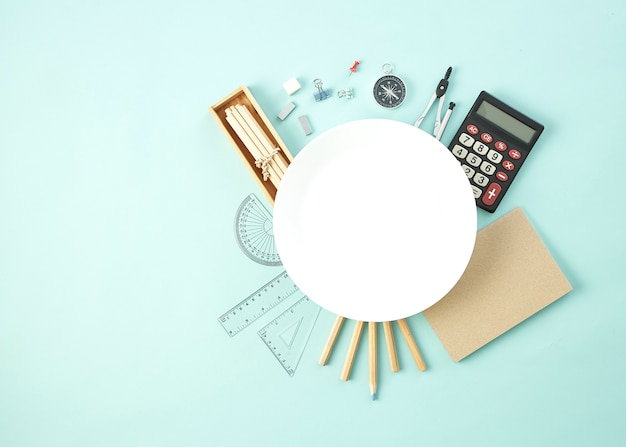 Przybory szkolne wokół pustego białego naczynia