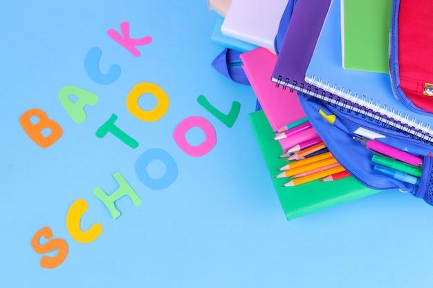 Przybory szkolne wypadające z plecaka szkolnego na niebieskim tle