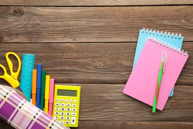 Przybory szkolne z notatnikiem na szarym tle. powrót do szkoły. leżał płasko. widok z góry