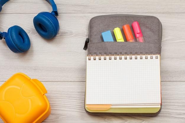 Przybory szkolne. żółte pudełko na kanapki, słuchawki, otwarty zeszyt na torbie-piórniku z kolorowymi pisakami i markerem na szarych drewnianych deskach. widok z góry z miejsca na kopię. powrót do koncepcji szkoły