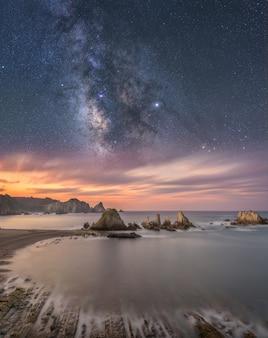 Przybrzeżny krajobraz w nocy z morzem i drogą mleczną na niebie
