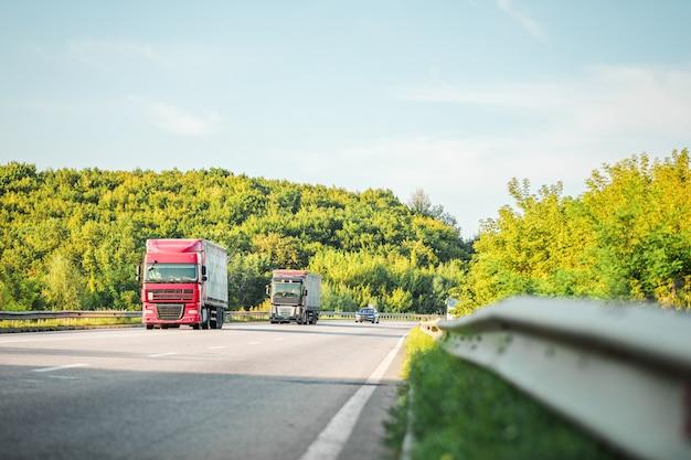 Przybywająca biała ciężarówka na drodze w wiejskim krajobrazie przy zmierzchem
