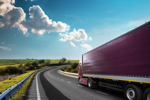 Przybywających biała ciężarówka na drodze w wiejski krajobraz o zachodzie słońca