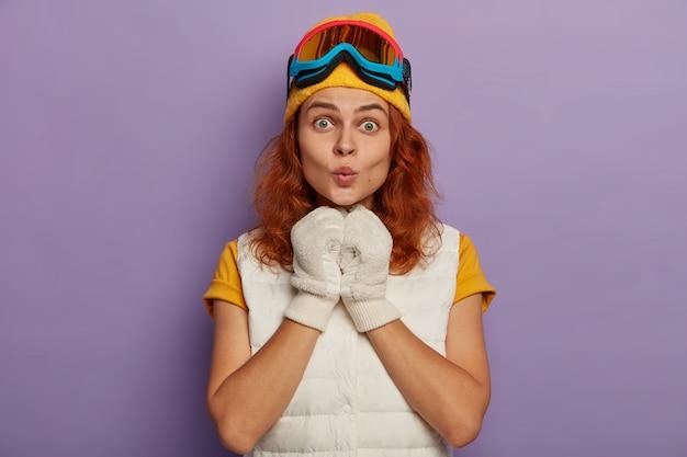 Przyciągająca rudowłosa kobieta nosi ciepłą czapkę, gogle narciarskie i biały sweter